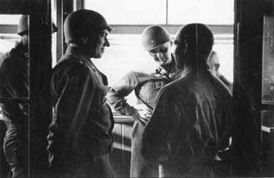 To the left, leaning on the doorframe, commander of the liberated camp of Gusen Lt. Col. Milton W. Keach, at the center, wearing sunglasses, his deputy Major Charles R. Sandler during a talk with former prisoners in Gusen. (photo credits: Courtesy of Maj. Charles R. Sandler, US 11th Armored Division, 21st Armored Infantry Battallion)