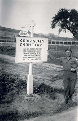 US soldier in front of sign indicating mass grave. (photo credits: US Signal Corps Foto, Courtesy of USHMM)