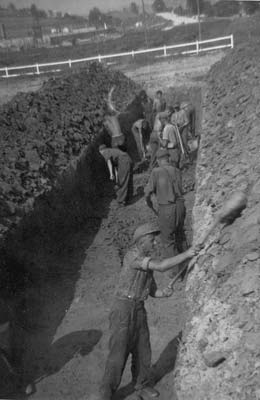 "Soldiers of the German ""Wehrmacht"" digging graves; apart from the local population also German POWs were brought in for the burial of dead prisoners in Gusen. (photo credits: US Signal Corps Photo, Courtesy of USHMM, Washington)"